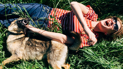 Photo of laughing woman with dog lying on lawn