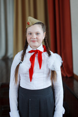 A modern girl with a red pioneer tie in a white shirt and a soldier's cap with a red star at a solemn meeting in honor of the Great Victory Day.