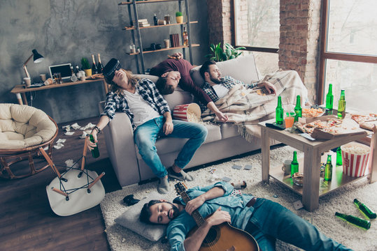 It was great party! Bearded, exhausted, tired, drunk guys are sleeping after night events on the floor and sofa in different pose in living room, having a lot of litter, garbage, rubbish around them