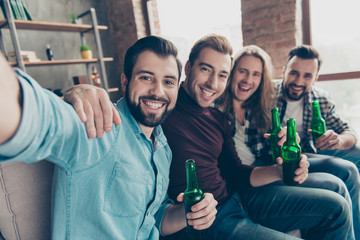 Self portrait of attractive, stylish, successful guys with modern hairstyle having bottles with lager in hands, shooting selfie while watching football match on tv, sitting in living room