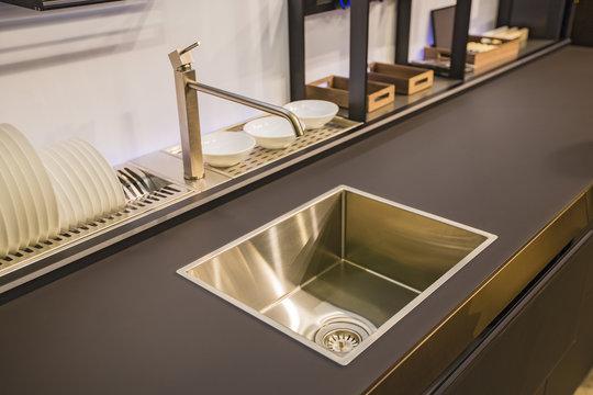 Kitchen faucet, modern kitchen in loft style, black table, gold luxury faucet kitchen