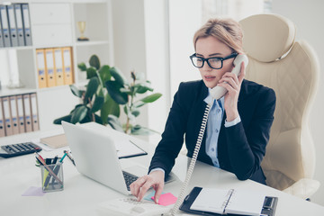 Connect line concept. Portrait of stylish smart lawyer in eyewear speaking by telephone using handset dialing number calling partners sitting in modern work place