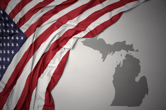 waving national flag of united states of america on a gray michigan state map background.
