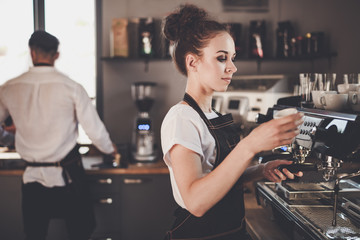 Young woman barista preparing coffee using machine in the cafe
