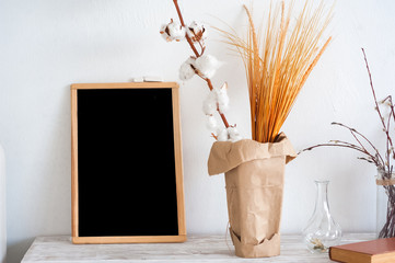 Black graphite chalkboard and a vase with a branch of cotton