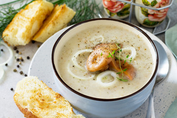 Diet menu. Puree soup mushrooms with croutons in a bowl on a light slate background. The concept of healthy eating.
