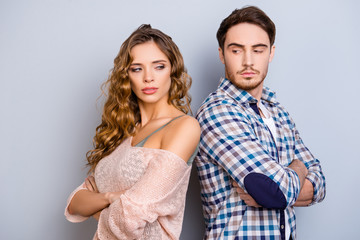 Portrait of upset unhappy couple standing back to back holding arms crossed ignoring each other isolated on grey background
