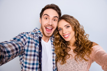 Self portrait of cheerful positive couple keeping mouth open shooting selfie on front camera having online meeting isolated on grey background