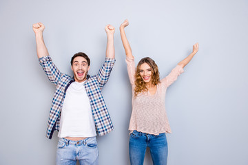 Portrait of stylish couple in casual outfits wearing jeans holding hands up celebrating achievement isolated on grey background
