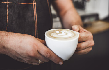 Latte art, professional barista presenting cup of coffee