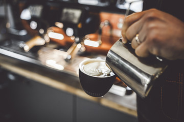 Coffee latte art, barista pouring milk into cup