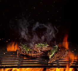 Poster Grill / Barbecue Beef steaks on the grill with flames