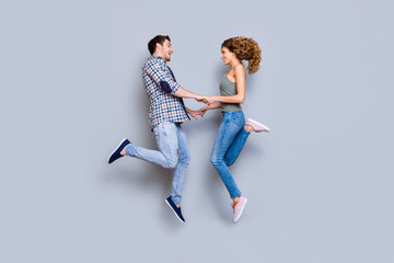 Profile portrait of playful joyful couple in denim outfits sneakers holding hands jumping in air enjoying holiday together isolated on grey background