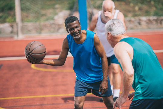 multiracial elderly men playing basketball together on playground on summer day