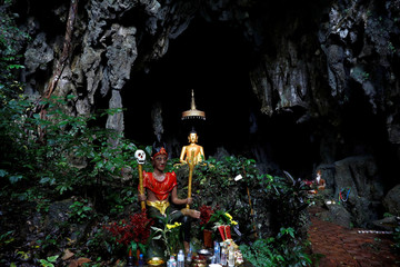 A spirit and Buddha state image seen in front of a cave near Tham Luang cave complex, as an ongoing search for members of an under-16 soccer team and their coach continues, in the northern province of Chiang Rai