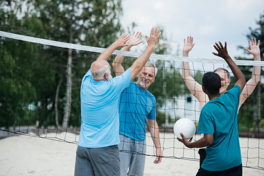 smiling multiethnic old volleyball players giving high five to each other after game