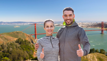 fitness, sport and gesture concept - smiling couple outdoors showing thumbs up over golden gate bridge in san francisco bay background