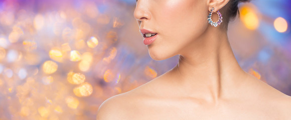 beauty, jewelry and luxury concept - close up of beautiful woman face with earring over holidays lights background