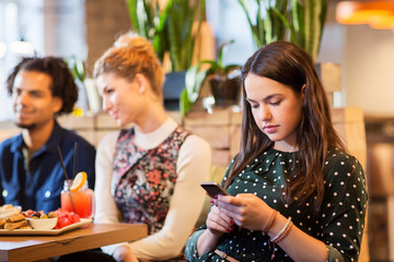 technology, lifestyle and people concept - woman with smartphone and friends at restaurant