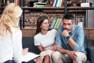 woman embracing stressed husband on therapy session by female counselor in office