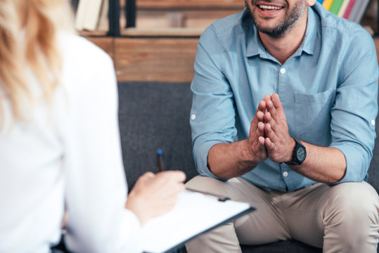 cropped image of female counselor writing in clipboard and smiling male holding hand palms together during therapy session in office