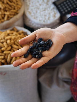 Fabric bags of dry fruits and hand with raisins