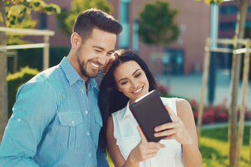 Happy young caucasian couple with tablet outdoors
