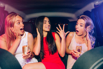 Brunette girl in red dress is showing ring on her finger. She is happy and proud. Her friends are very excited. They are impressed. Blonde girls are holding glasses of champagne in hands.