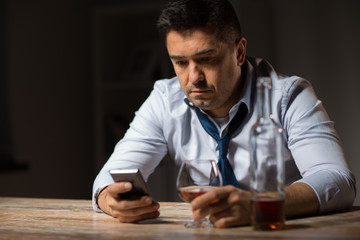 alcoholism, alcohol addiction and technology concept - male alcoholic with smartphone and glass of brandy at night
