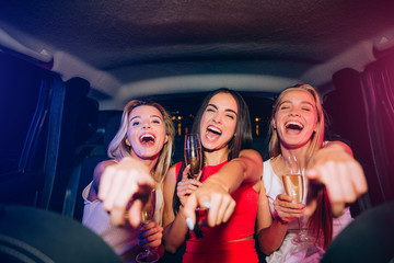 Happy and excited girls are sitting together in car. They are looking and pointing on camera. Young women are laughing and smiling. Some of them has a glass of champagne in hands.