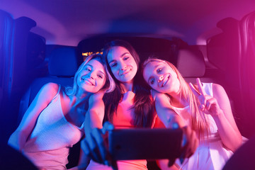 Nice and cheerful girl are sitting in car together. Blonde girls are resting on their friend's shoulders. Brunette is holding black phone. She is taking selfie. Young women are looking on phone.