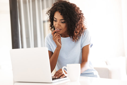 Pensive african woman using laptop computer