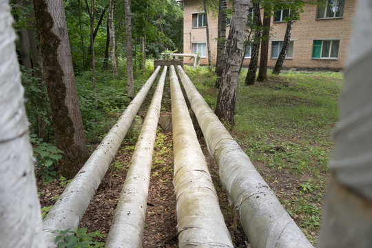 Laying of heat-insulated large diameter pipes for hot water supply during the construction of a residential area. Pipes are insulated with special materials. Are above the ground.