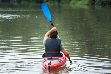 Adult male canoeing on mountain lake