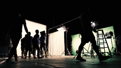 Behind the scenes of TV commercial movie film or video shooting production which crew team and camera man setting up green screen for chroma key technique in big studio.