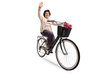 Mature woman riding a bicycle and waving at the camera