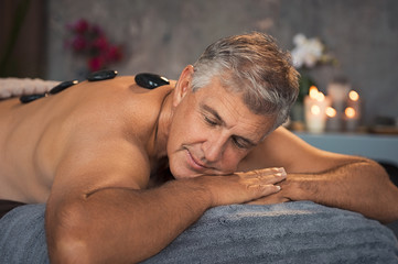 Senior man resting with hot stone massage