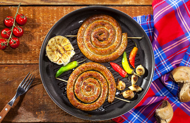 Grilled spiral sausages in a pan on wooden background