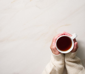 Woman holding cup of hot tea on stone beige table, hands in warm sweater with mug, winter morning concept, top view