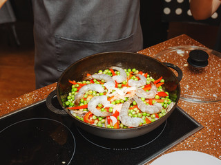 Cooking of a paella in pan in a kitchen