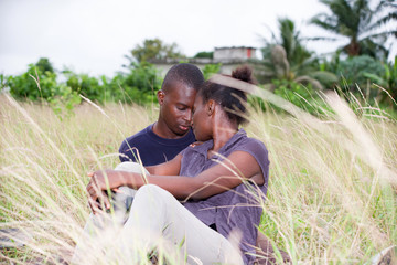 happy young couple in love relaxes sitting in the grass in summer.