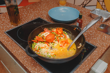 Cooking spanish paella at home or at restaurant