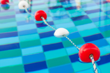 Red and white floats on rope in pool