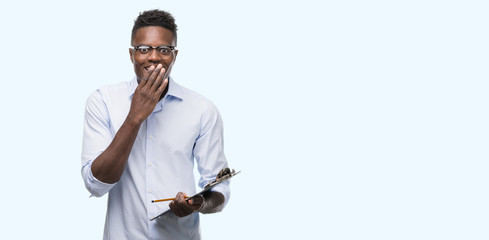 Young african american man holding a clipboarad cover mouth with hand shocked with shame for mistake, expression of fear, scared in silence, secret concept