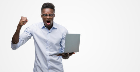 Young african american businessman using computer laptop annoyed and frustrated shouting with anger, crazy and yelling with raised hand, anger concept