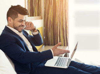 Businessman talking on phone and using laptop in hotel room