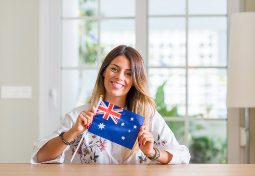 Young woman at home holding flag of Australia with a happy face standing and smiling with a confident smile showing teeth