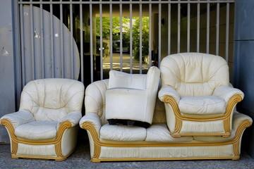 Canapés et fauteuils jetés dans la rue. Encombrants.