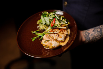 Tattoed bartender holding a plate of chicken fillet and salad