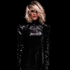 portrait of sensual blonde woman wearing black shiny dress